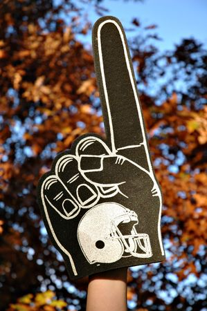 A #1 football foam finger set against autumn leaves and a blue sky