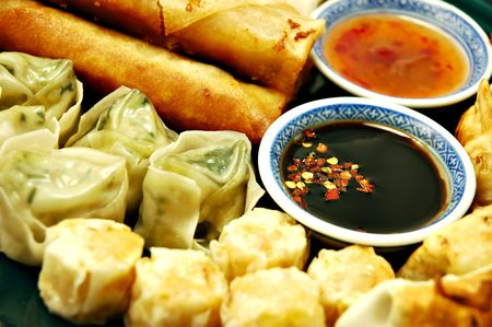 sum: Plate of dim sum, egg rolls, shumai, and pot stickers with dipping sauce Stock Photo