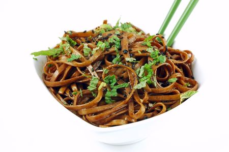 Bowl of stir fried udon noodles garnished with black sesame seeds and fresh mint with green chopsticks isolated on a white background