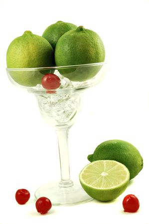 margarita glass: Margarita glass filled with sliced limes and cherries isolated on a white background Stock Photo