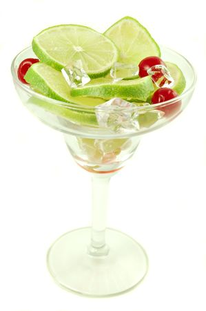 Margarita glass filled with sliced limes and cherries isolated on a white background photo