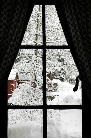 Kijkend door een oude hut venster op vers gevallen sneeuw