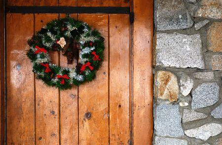 log cabin winter: Christmas wreath hanging on a rustic wooden door Stock Photo