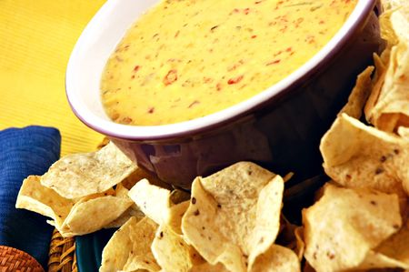 dipping: Bowl of warm queso (cheese dip) with a plate of tortilla chips