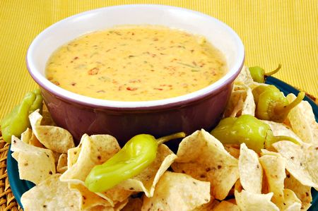 Bowl of warm queso (cheese dip) with a plate of tortilla chips