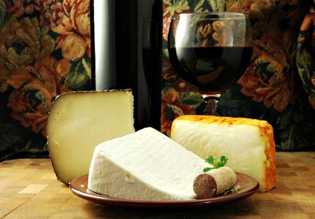 cheeses: Three cheeses with a bottle and glass of red wine