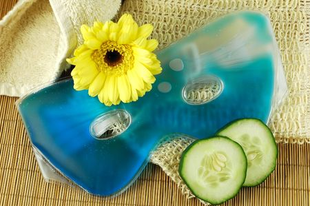 soothe: Soothing blue eye mask with cucumber slices, towel, natural fiber cloth, and yellow daisy on a bamboo mat