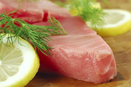 Fresh tuna steaks with lemon and dill on a cutting board Stock Photo