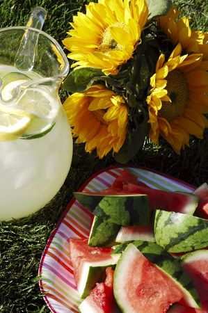 Pitcher of lemonade, plate of watermelon, vase of sunflowers on grass in summer afternoon sunlight  photo