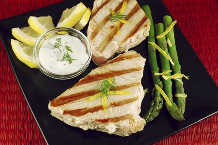 Grilled tuna steak dinner on a black plate with asparagus, lemon, and yogurt dill sauce Stock Photo