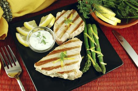 Grilled tuna steak dinner with table setting, bowl of lemon and dill, asparagus, and yogurt dill sauce