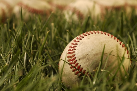 Nostalgic baseballs in the grass on a baseball field  Stock Photo