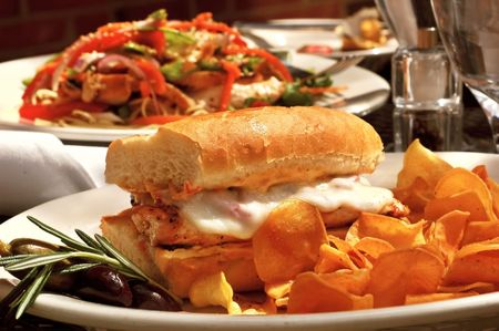 chicken sandwich: Grilled chicken sandwich with melted provolone and sweet potato chips served at an outdoor restaurant