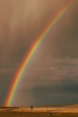 Rainbow emerging from the town of Elko, Nevada, in a rain storm over farmland and desert photo