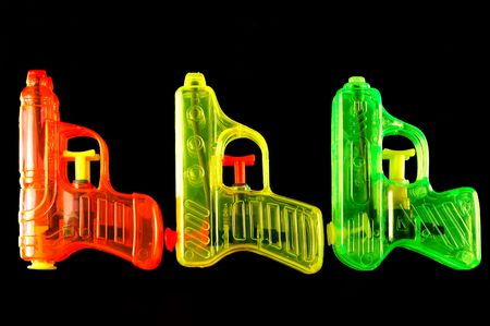 mirrored: Three toy squirt guns isolated on a black mirrored background
