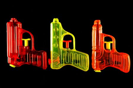 Three toy squirt guns isolated on a black mirrored background