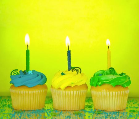 Three birthday cupcakes in blue, green, and yellow with lit candles, confetti, and sprinkles on a mirrored background Stock Photo - 902426