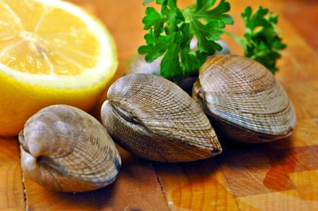 clams: Three raw clams ready for steaming on a kitchen cutting board with lemon and parsley
