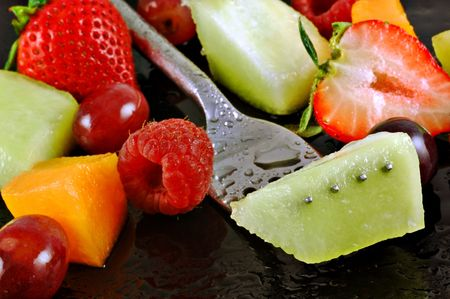 Variety of fresh fruit prepared for a salad on a watery black plate