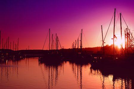 Sun setting behind an oceanfront marina Imagens