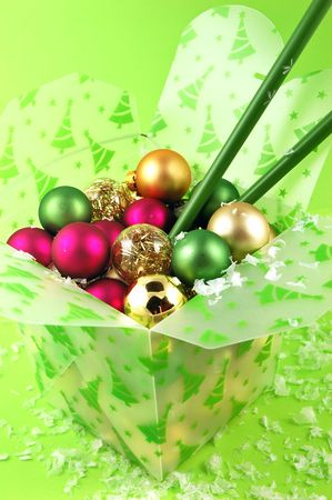 Christmas ornaments in a take-out food container with chopsticks on a lime green background photo