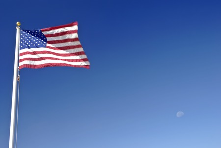 billowing: American flag billowing against a deep blue clear sky with the moon in the background Stock Photo