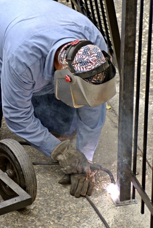 metal post: Fence installation worker welds a seal on a new fence post