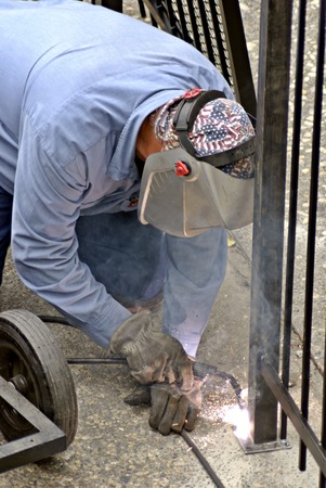 Fence installation worker welds a seal on a new fence post