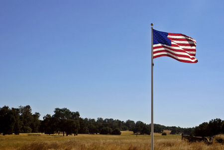 billowing: American flag billowing in a deep blue clear sky in Gold Rush Country in the Sierra Foothills of California