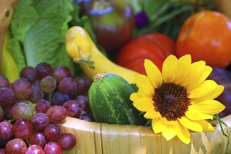 bounty: La cesta de mimbre llenó de las frutas, vehículos y florece fresco del jardín