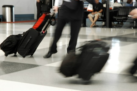 Travelers in motion rushing through an airport photo