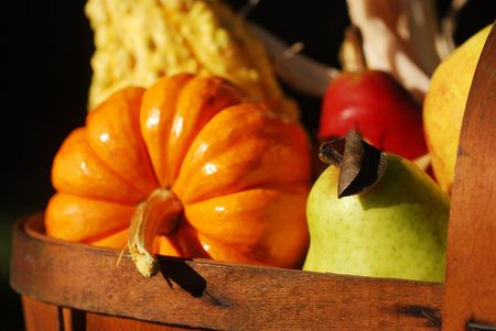 Vintage wooden fruit basket filled with autumn fruits and vegetables outdoors in sunlight photo