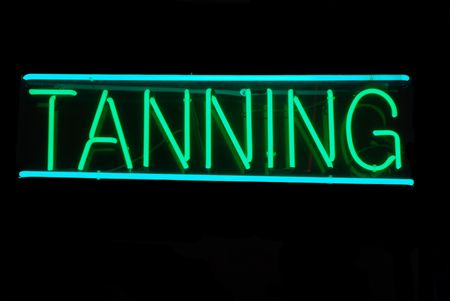 Illuminated green and blue tanning neon sign on black Stock Photo - 2090279