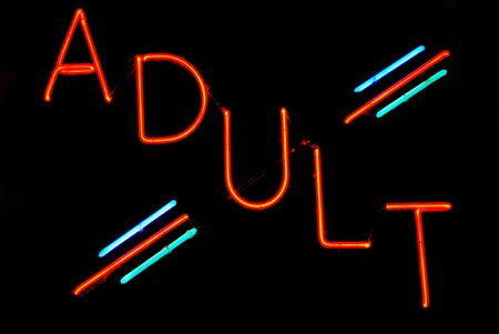 porno: Beleuchtete Erwachsene Leuchtreklame auf schwarzem Hintergrund Lizenzfreie Bilder