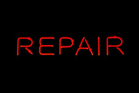 shop sign: Illuminated red repair shop neon sign on black