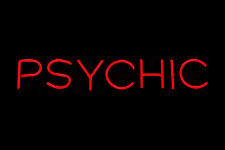 Illuminated red psychic neon sign on black photo