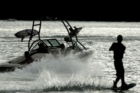ウエイクボーダー夕暮れ時に水にボートの後ろにスキー