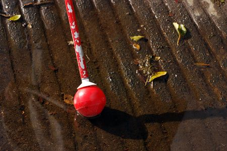 visually: Blind persons white cane in a puddle at a curb cut