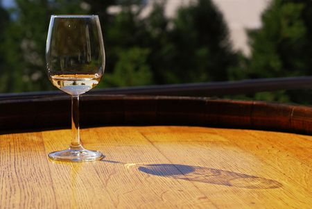 Glass of white wine on a wooden barrel