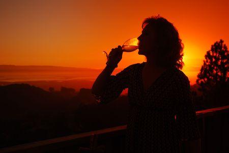 sorbo: Hermosa mujer de mediana edad de beber un vaso de vino blanco en su cubierta a la puesta del sol