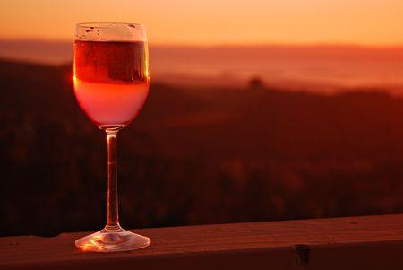 日没で木製レールにバラのワインのガラス 写真素材