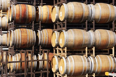 Wine barrels stacked in rows outdoors at a winery