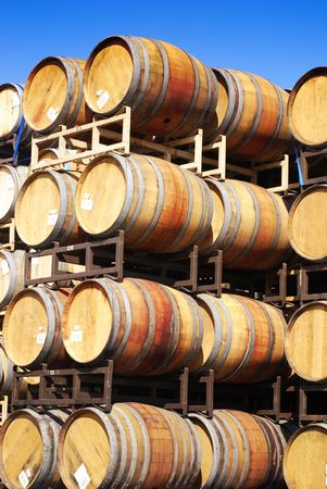 Wine barrels stacked high against a clear blue sky