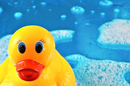 Toy rubber duck swimming in soap bubbles on a shiny watery blue background photo