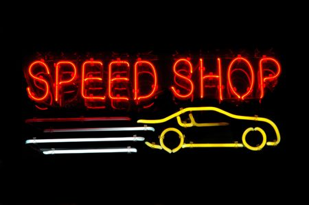 Neon sign advertising a speed shop with a racing car photo