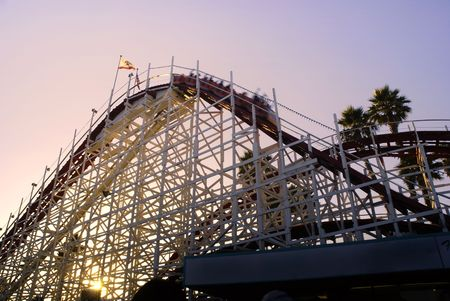 People riding on the Big Dipper rollercoast as the sun sets behind it, Santa Cruz Beach Boardwalk, California photo