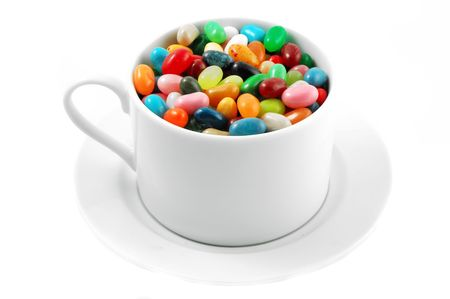 Jelly beans in a white coffee cup and saucer isolated on white photo