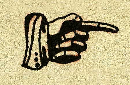 Vintage style hand with finger pointing sign painted on a stucco wall