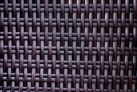 threaded: Black plastic thread woven on the back of a patio chair Stock Photo