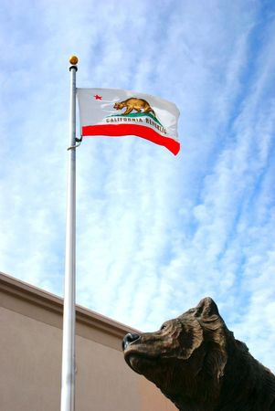 Bronze statue of a bear looking skyward at the California State flag with the Golden State Bear photo